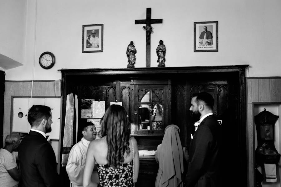 Zakrystia świadkowie z panem młodym i księdzem