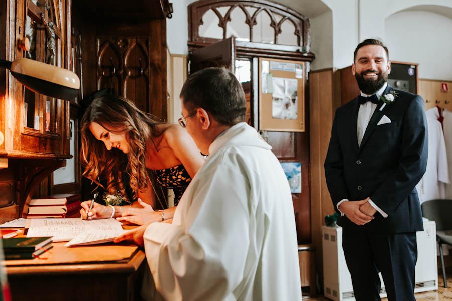 Świadkowie podpisują dokumenty w zakrystii